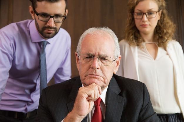 Hombre mayor de negocios pensativo mientras un hombre y una mujer le observan