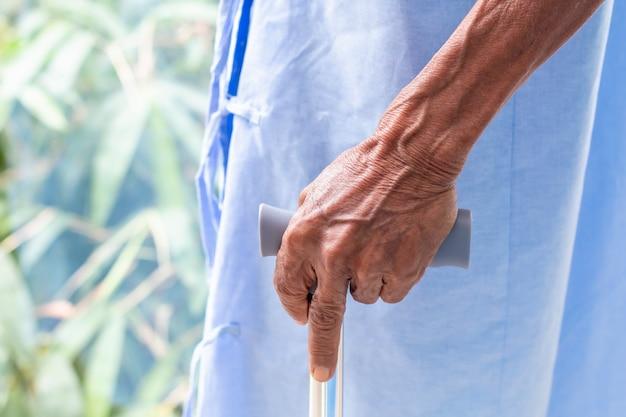 Hombre mayor paciente con bastón en la habitación del hospital.