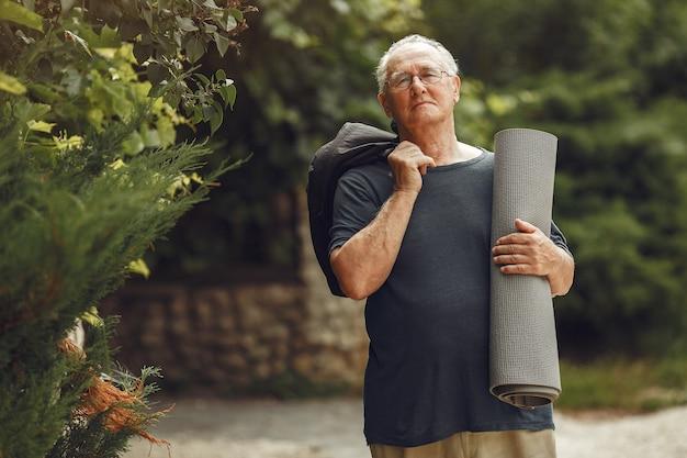 Hombre mayor en el parque de verano. grangfather con una estera.