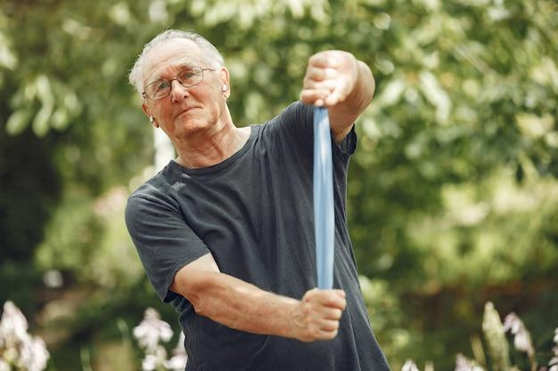 Hombre mayor en el parque de verano. grangfather usando un borrador.