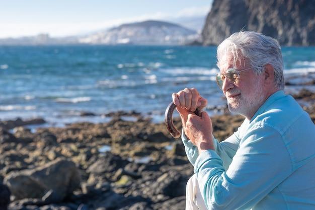 Hombre mayor, de pelo blanco, sosteniendo un bastón sentado en la playa mirando al horizonte sobre el agua
