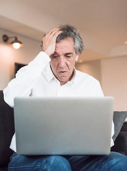 Hombre mayor preocupado que se sienta en el sofá que mira la computadora portátil
