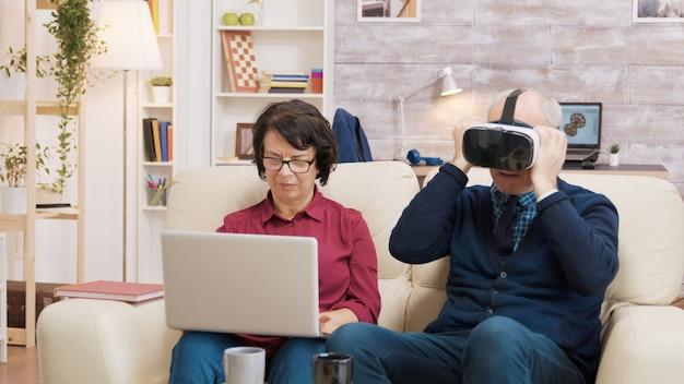 Hombre mayor probando un visor de realidad virtual en la sala de estar mientras su esposa usa una computadora portátil junto a él. pareja de ancianos modernos usando tecnología