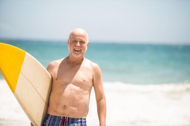 Hombre mayor, proceso de llevar, tabla de surf