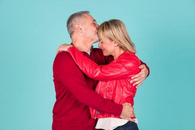 Hombre mayor que se besa en la cabeza de su esposa que abraza contra fondo coloreado