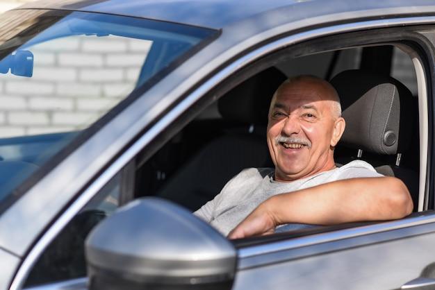Hombre mayor que conduce un coche, mirando a la cámara.