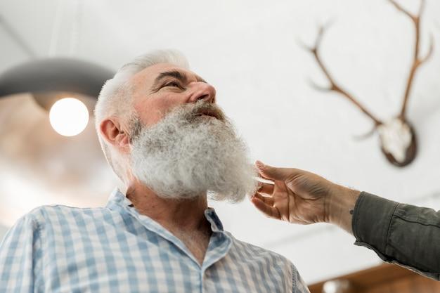 Hombre mayor que consulta en el ajuste de la barba en salón