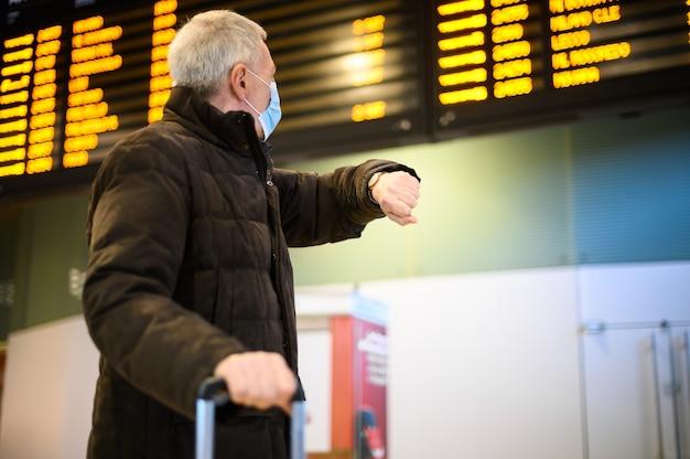 Hombre mayor que llevaba una máscara protectora contra covid 19 en una estación de tren comprobando la hora