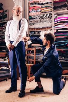 Hombre mayor que mira al diseñador de moda de sexo masculino que toma la medida de sus bragas en la tienda
