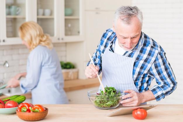 Hombre mayor que mira la tableta digital que prepara la ensalada verde en el bol de vidrio y su esposa que trabaja en el fondo