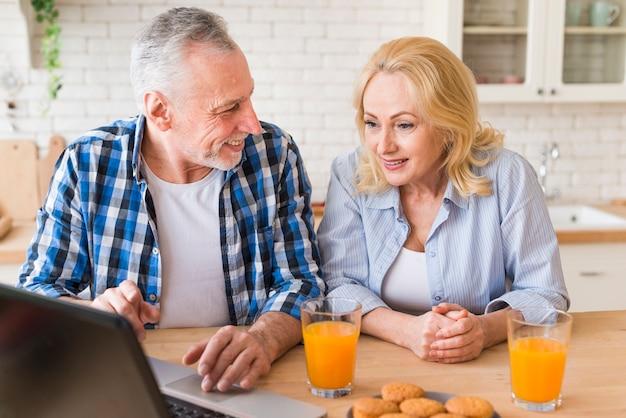 Hombre mayor que muestra algo a su esposa en la computadora portátil con el jugo de cristal y los molletes en la tabla