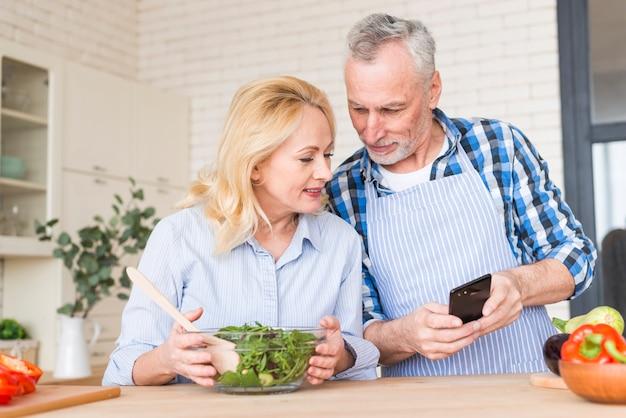 Hombre mayor que muestra algo a su esposa en el teléfono móvil en la cocina