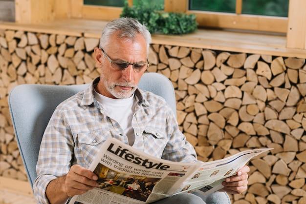 Hombre mayor que se sienta en el periódico de la lectura de la silla cerca de la ventana