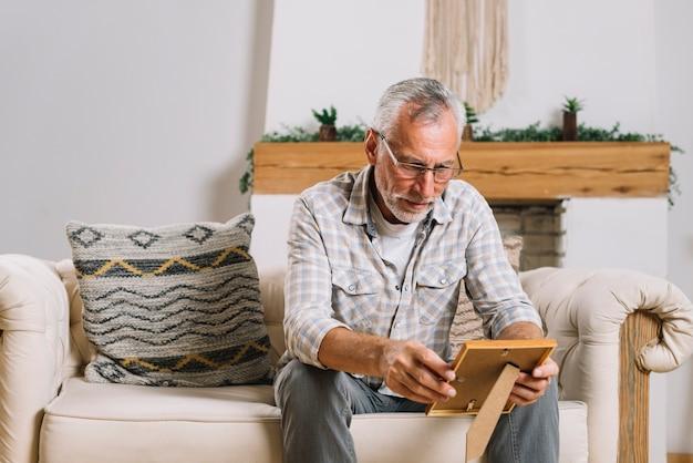 Hombre mayor que se sienta en la sala de estar que mira el marco de la foto
