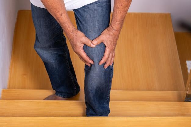 Hombre mayor que sube las escaleras en casa y se toca la rodilla por el dolor de la artritis