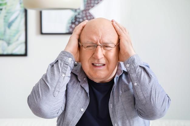 Hombre mayor que sufre de dolor de cabeza en casa