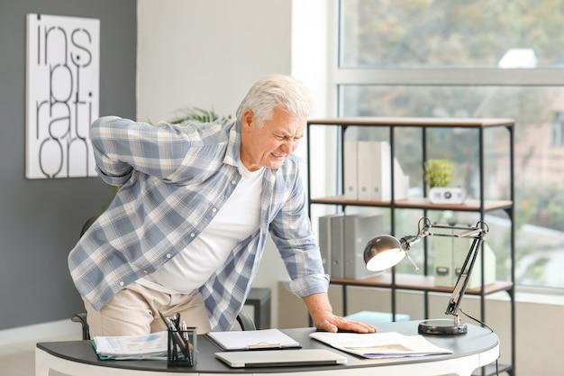Hombre mayor que sufre de dolor de espalda en casa