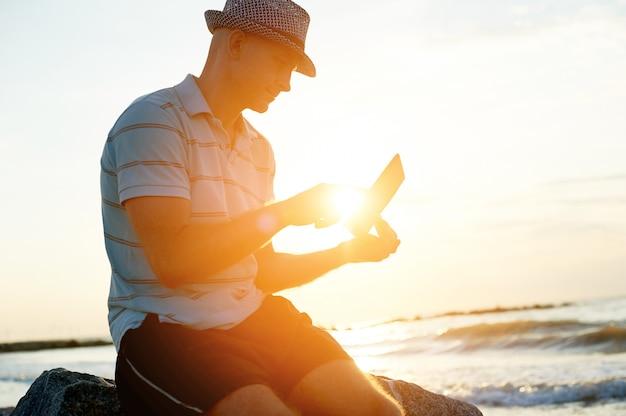 Hombre mayor que trabaja en su computadora portátil en la playa durante puesta del sol