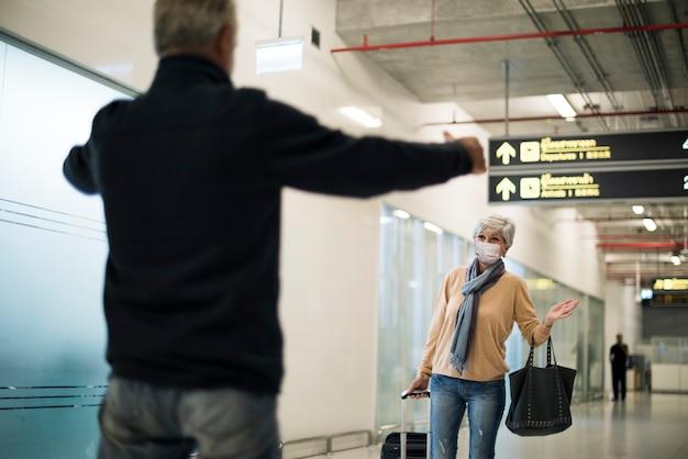 Hombre mayor recogiendo a su esposa en el aeropuerto después del cierre del covid-19