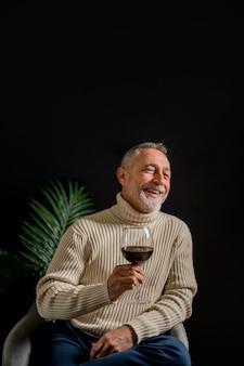 Hombre mayor riendo con copa de vino