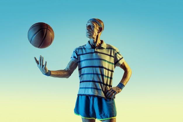 Hombre mayor con ropa deportiva jugando baloncesto sobre fondo degradado, luz de neón.