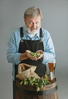 Hombre mayor seguro cervecero con cerveza artesanal en vidrio en barril de madera en la pared gris. dueño de fábrica presentó sus productos, probando calidad.