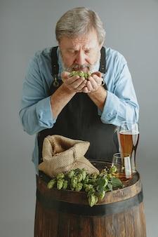 Hombre mayor seguro cervecero con cerveza artesanal en vidrio en barril de madera en la pared gris