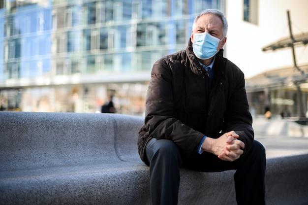 Hombre mayor sentado al aire libre con una máscara protectora contra la pandemia de coronavirus