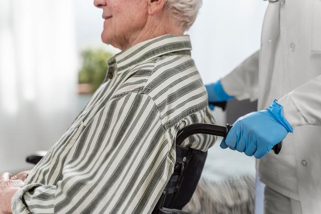 Hombre mayor sentado en silla de ruedas junto a un médico