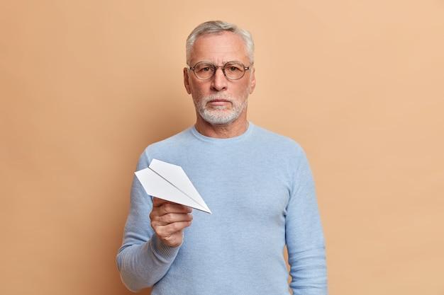 Hombre mayor serio con barba gruesa sostiene el avión de papel mira con confianza al frente sostiene el avión de papel usa gafas ópticas puente casual posa sobre una pared beige