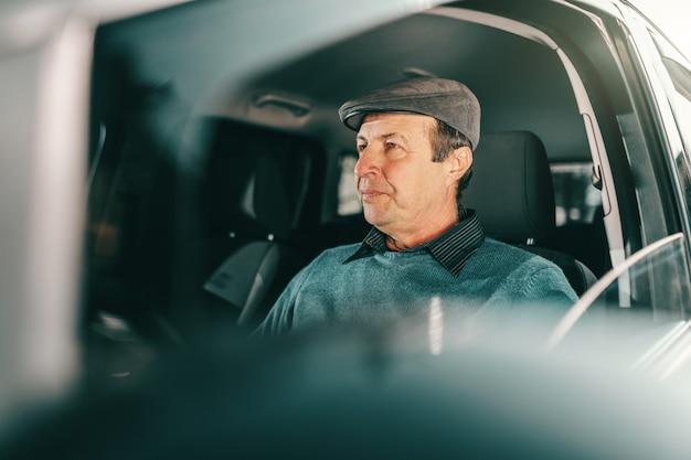 Hombre mayor serio caucásico con gorra en la cabeza, sentado en un coche caro