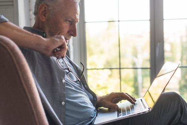 Hombre mayor serio que usa la computadora portátil en casa
