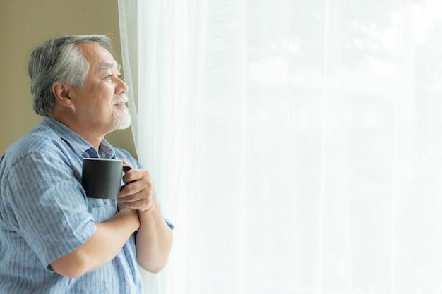 Hombre mayor siente feliz bebiendo café en la mañana, disfrutando el tiempo en su fondo interior de casa