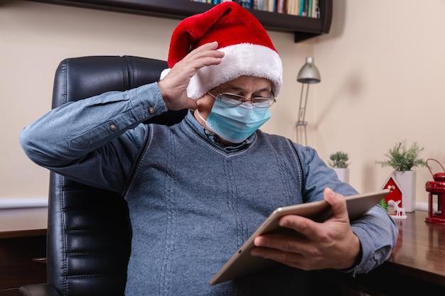 Hombre mayor con sombrero de santa claus habla con dispositivo de tableta para videollamadas amigos y niños. la habitación está decorada de forma festiva. navidad durante el coronavirus.