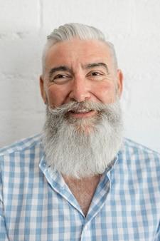 Hombre mayor sonriente en camisa en estudio