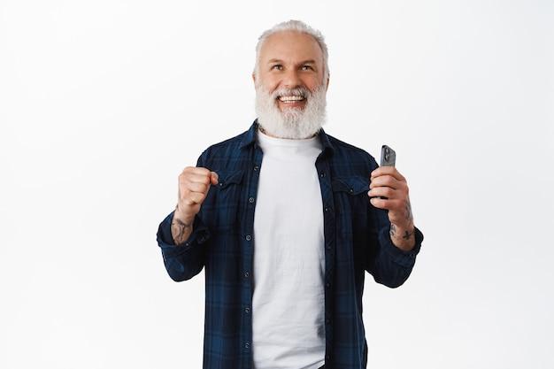 El hombre mayor sonriente dice que sí, levanta el puño, aprieta los puños en señal de triunfo y sostiene el teléfono inteligente, ríe mientras gana y celebra el éxito, logra el objetivo en línea en la aplicación, pared blanca
