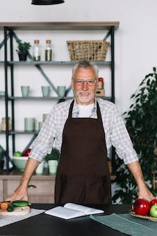 Hombre mayor sonriente que se coloca delante de contador de cocina