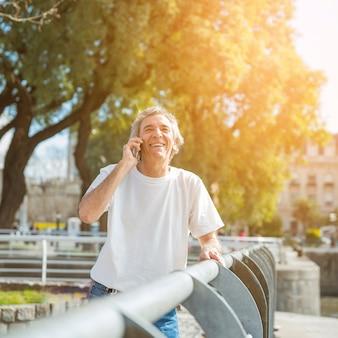 Hombre mayor sonriente que se coloca en el parque que habla en el teléfono móvil