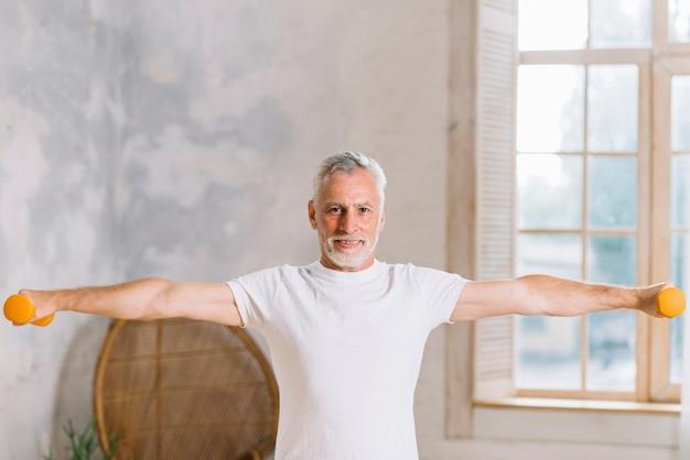 Hombre mayor sonriente que ejercita con pesas de gimnasia en casa