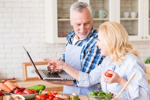 Hombre mayor sonriente que mira a su esposa que señala en el ordenador portátil mientras que prepara la ensalada en la cocina