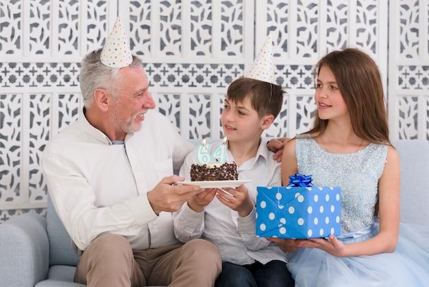 Hombre mayor sonriente que mira a sus nietos que sostienen la torta de cumpleaños deliciosa y la caja de regalo que se sientan en el sofá
