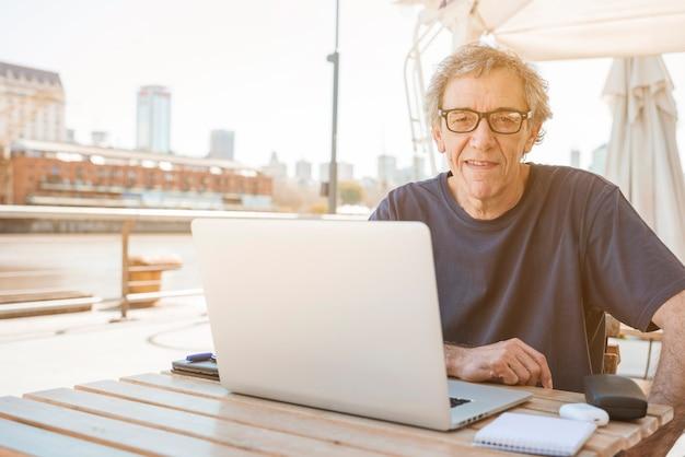 Hombre mayor sonriente que se sienta en restaurante con el ordenador portátil en la tabla