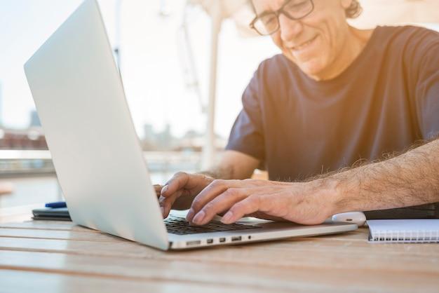 Hombre mayor sonriente que usa el ordenador portátil en el café al aire libre
