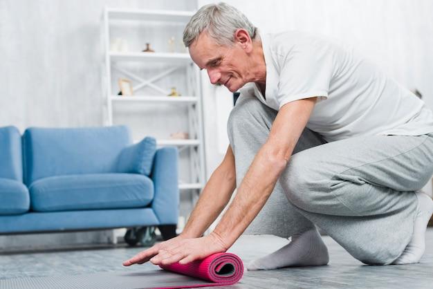 Hombre mayor sonriente rodando estera de yoga después de yoga en casa