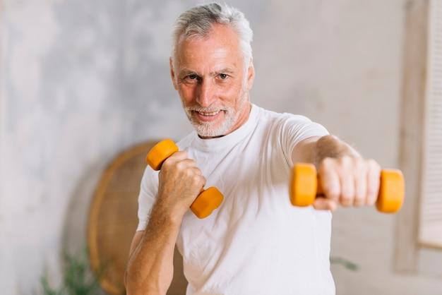 Hombre mayor sonriente sano que se resuelve con pesas de gimnasia