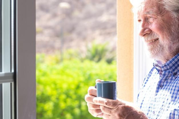Hombre mayor sonriente en la ventana sosteniendo una taza de café mirando hacia afuera