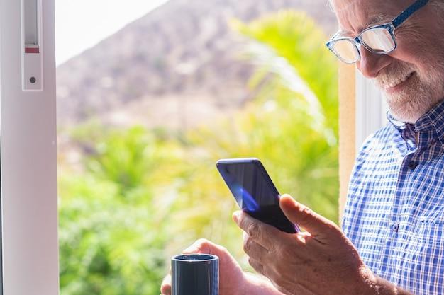 Hombre mayor sonriente en la ventana sosteniendo la taza de café mediante teléfono móvil