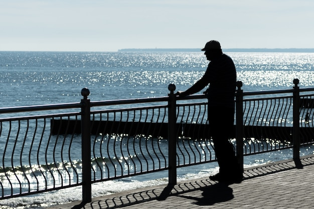 El hombre mayor sueña con aventuras de la vida, viajes pasados y mira al mar. vista posterior trasera, copia espacio. el viejo viudo del cáncer extraña a su esposa. tiempo soleado y mar azul limpio.