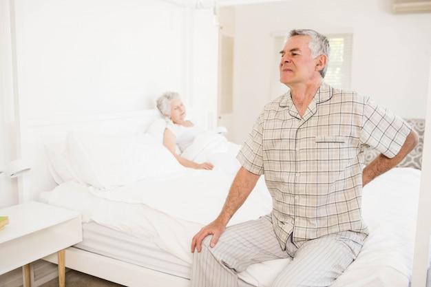 Hombre mayor sufriente que retiene su espalda en casa