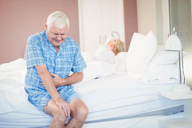 Hombre mayor sufriente sosteniendo su vientre en la cama